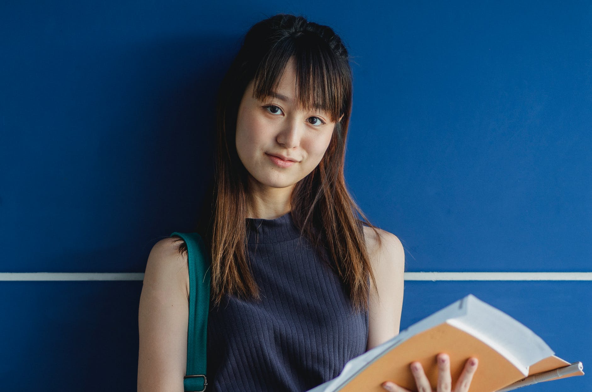 charming asian student with exercise books near blue wall